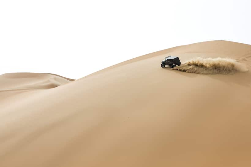 Off-road vehicle drives over undulating sand dunes