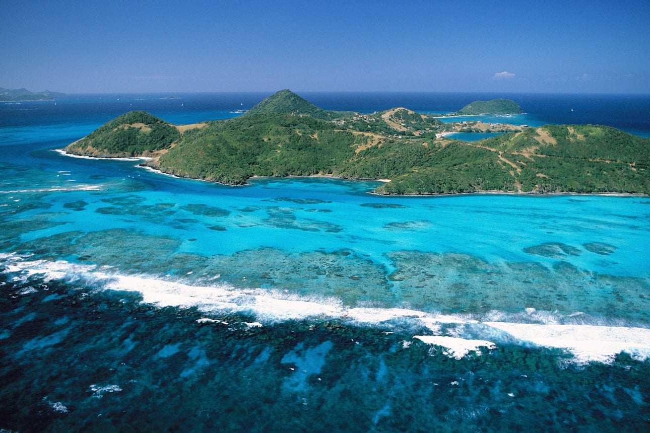 View of the lush green Canouan island surrounded by turquoise Caribbean Sea