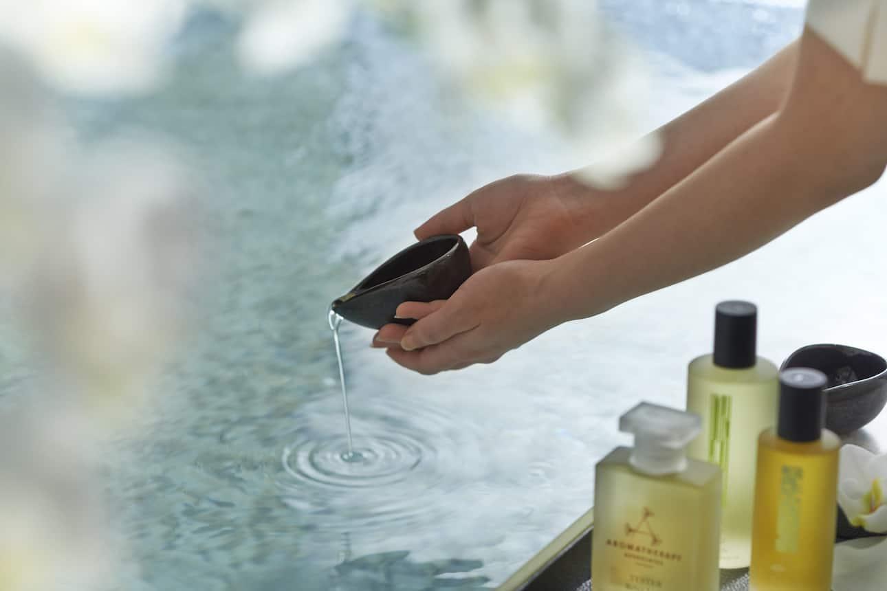 Hands pour essential oils into bath water