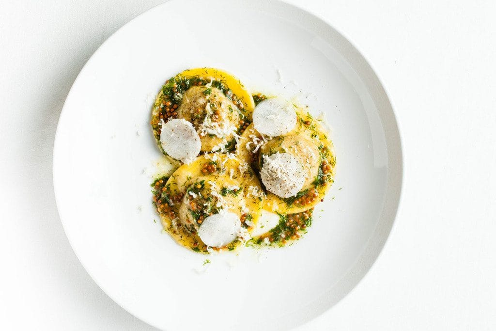 Pasta dish at Dovetail – three pieces of filled pasta on a white plate topped with cheese shavings and pesto