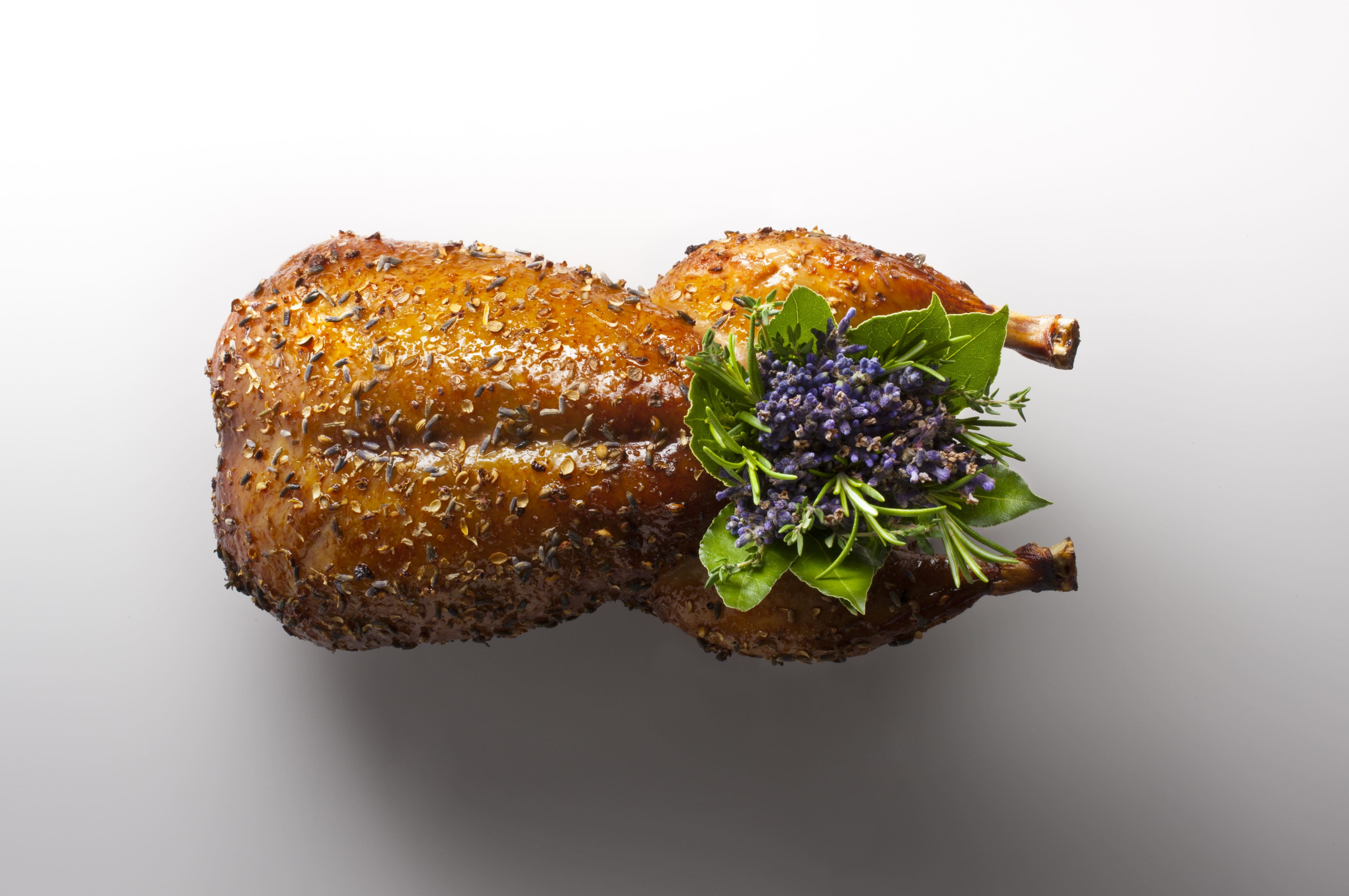 Dish at Eleven Madison Park – small roasted bird with green and purple floral decorations