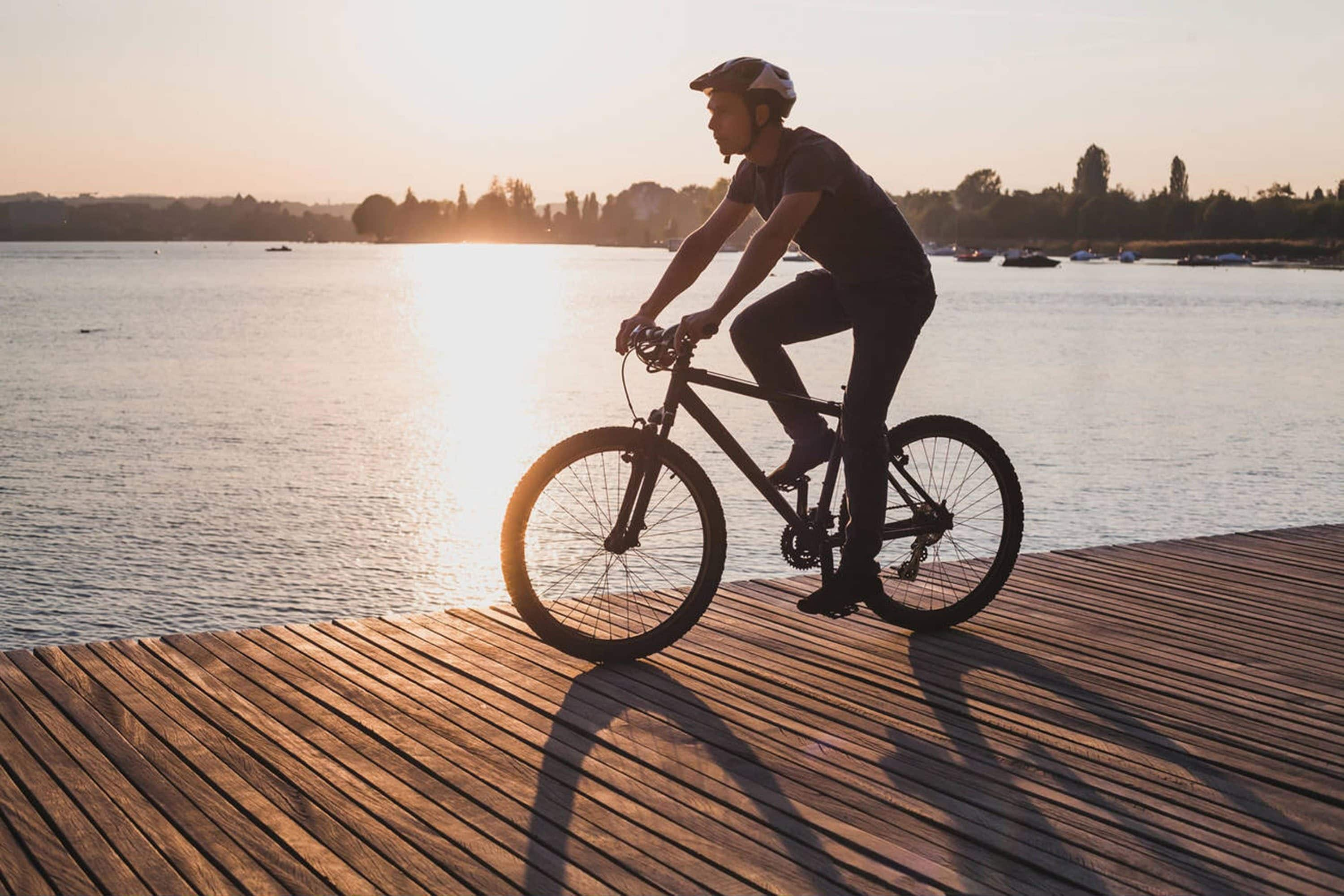 Man rides bike near a lake in the sunshine