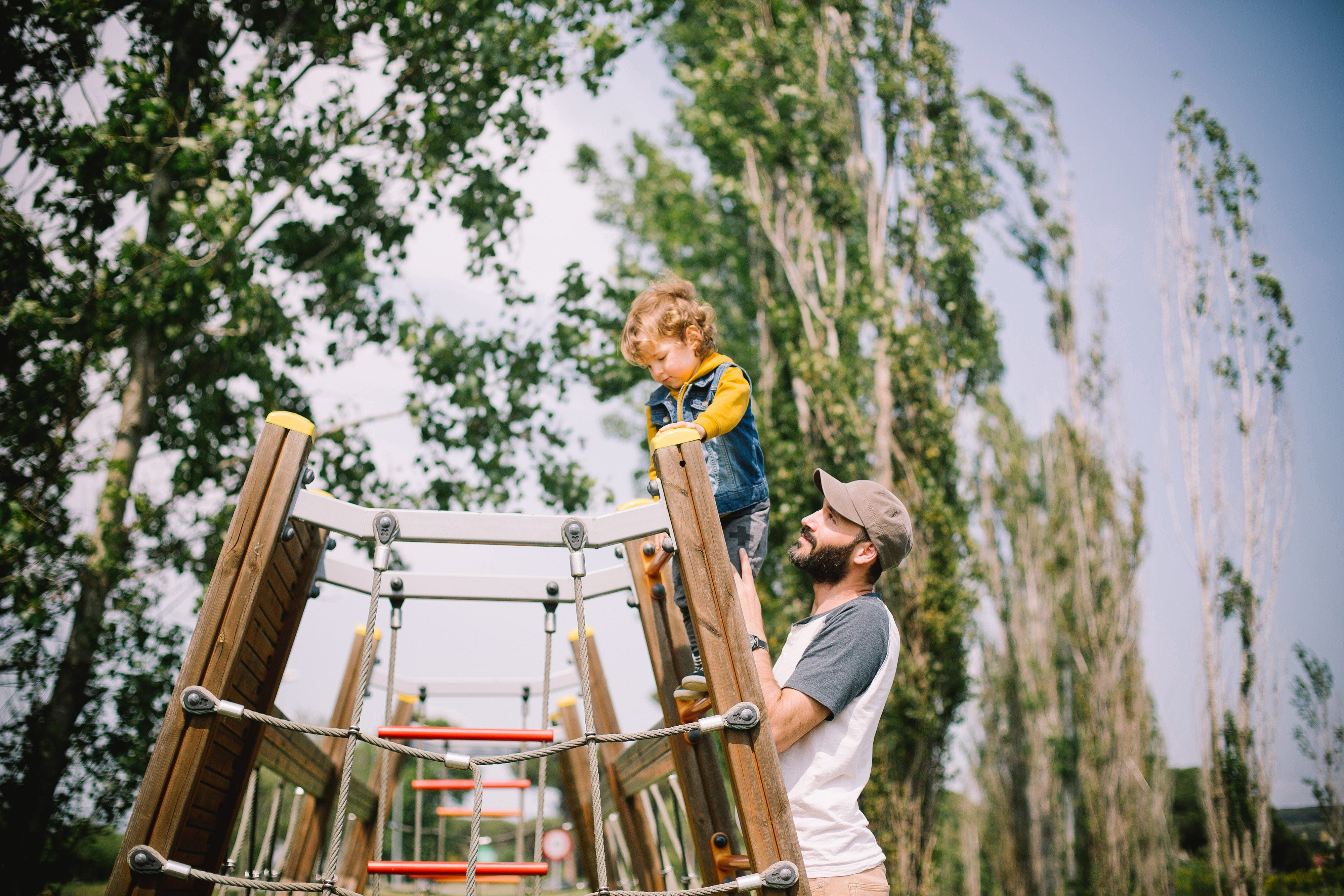 A small child scaling a climbing frame with its father at Gutovka sport center