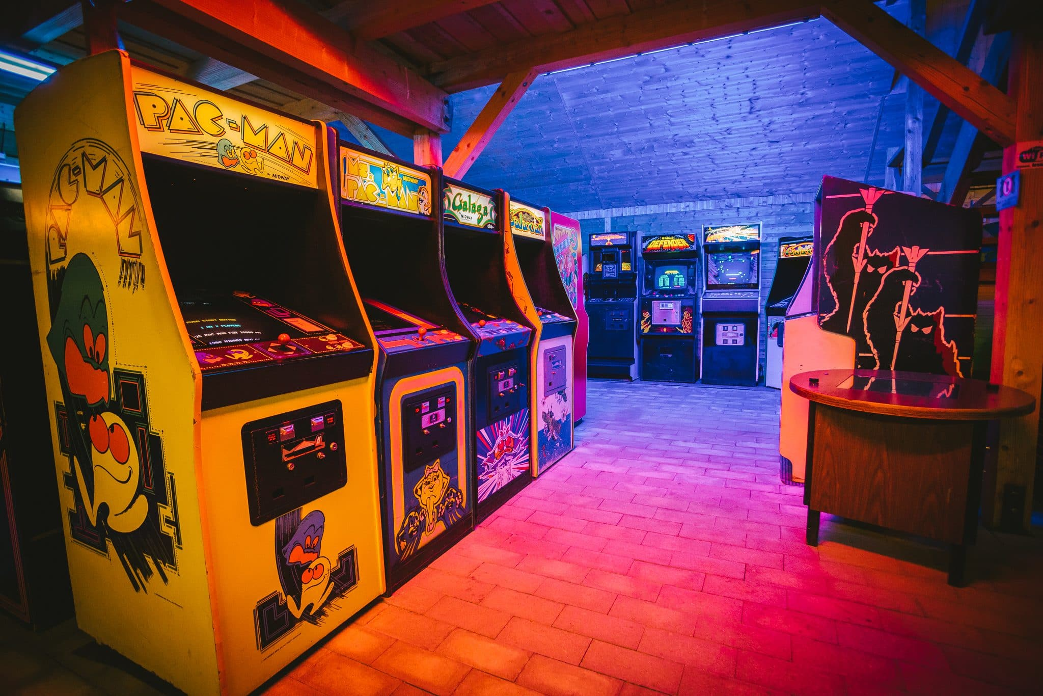 Old-school arcade game machines lined up in the Arcade Museum