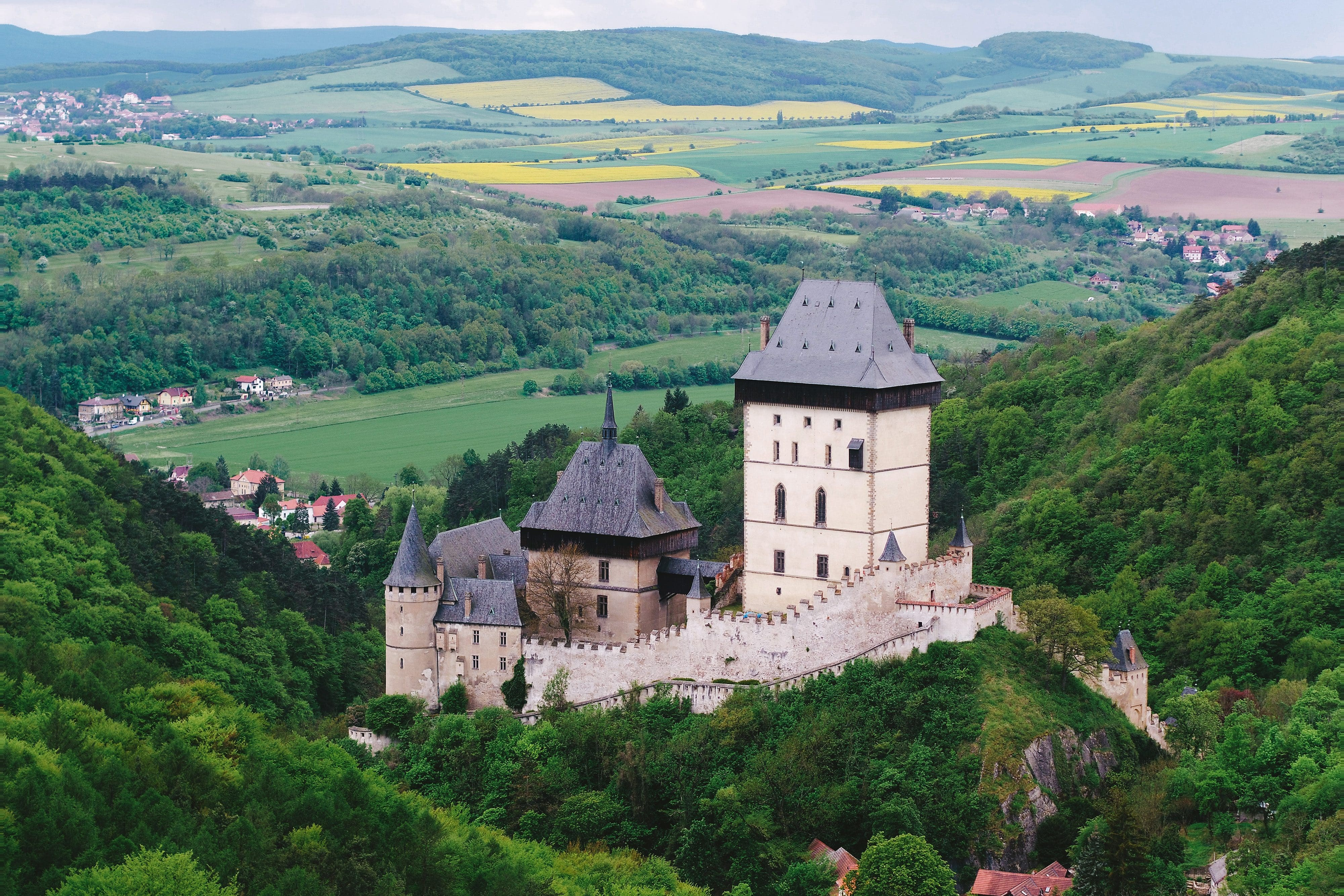 The towers and battlements of Karlštejn Castle peek out above the green landscape