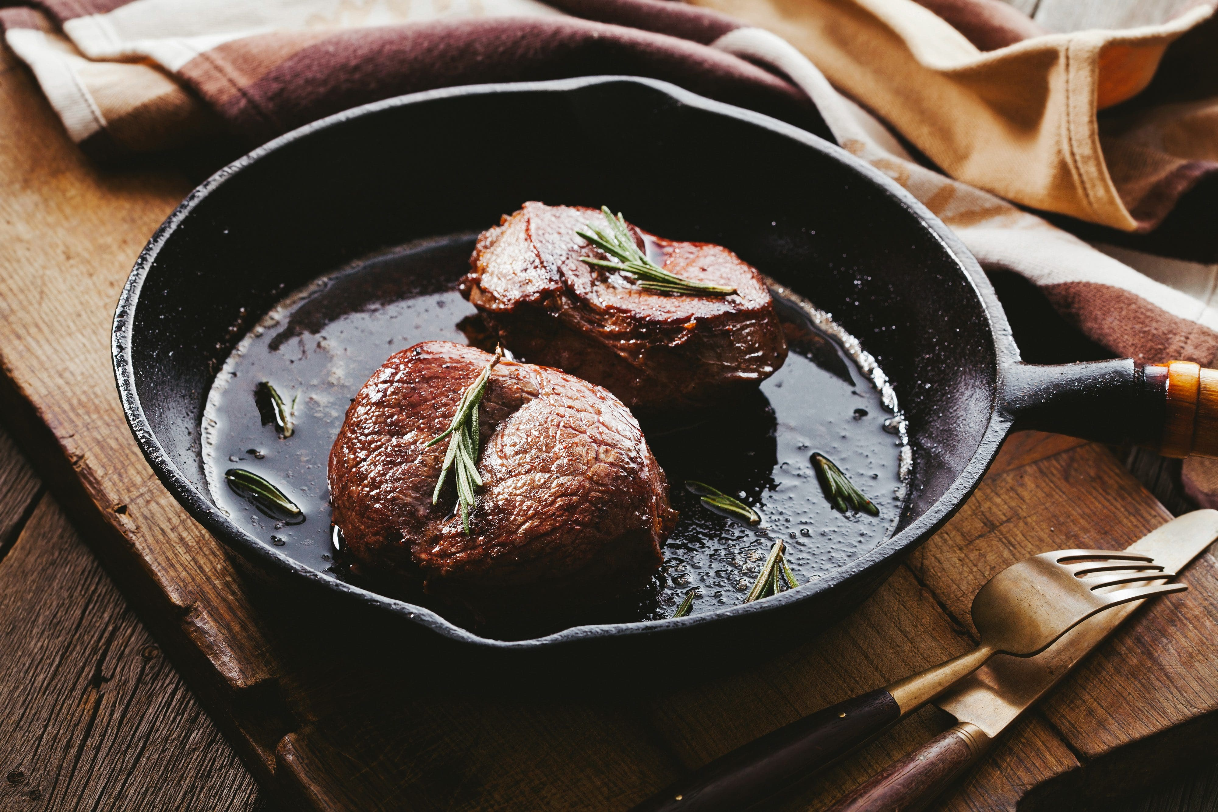 Two fillet steaks topped with rosemary in a skillet at Cocina Rivero