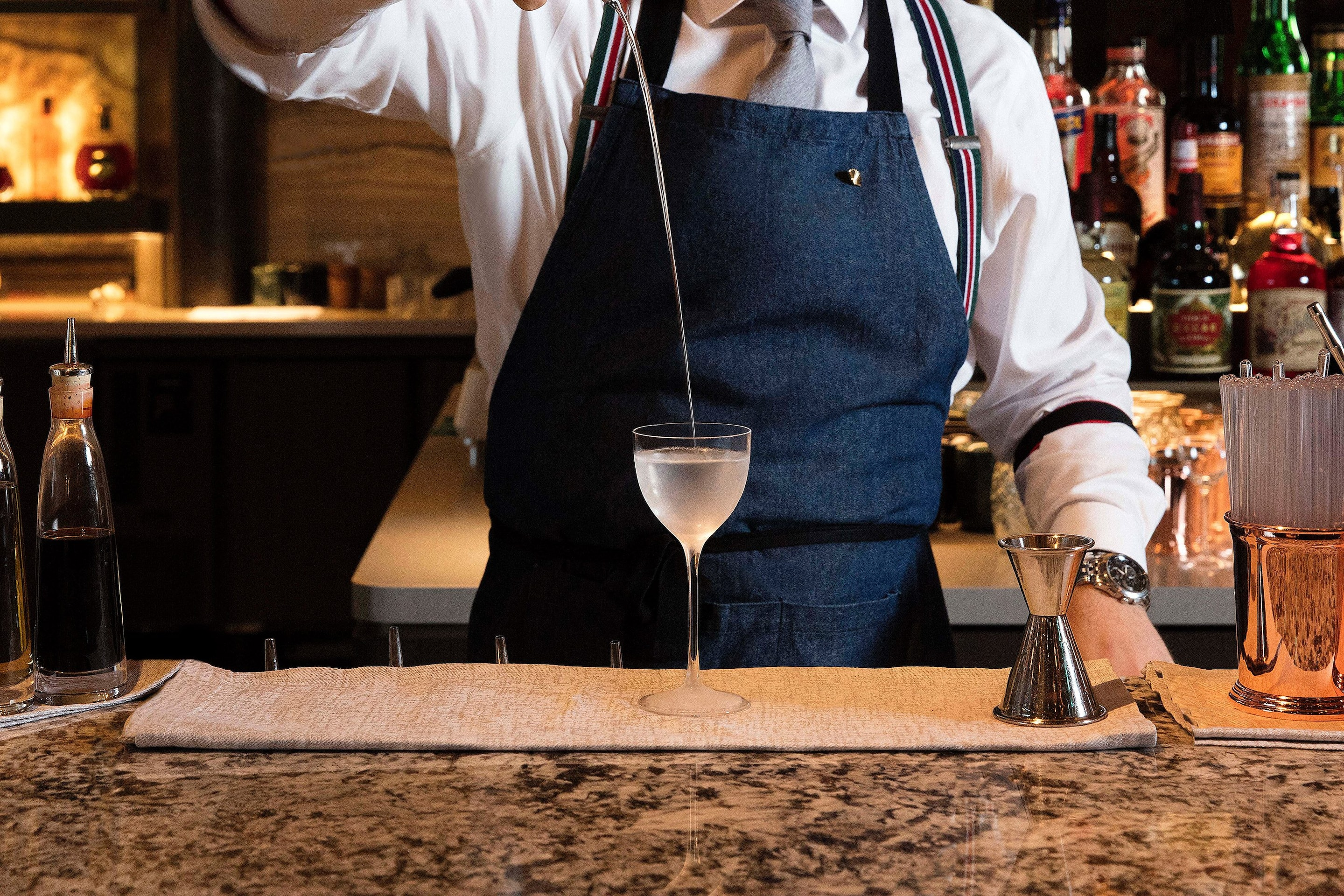 Bartender pours a cocktail into a glass from a height