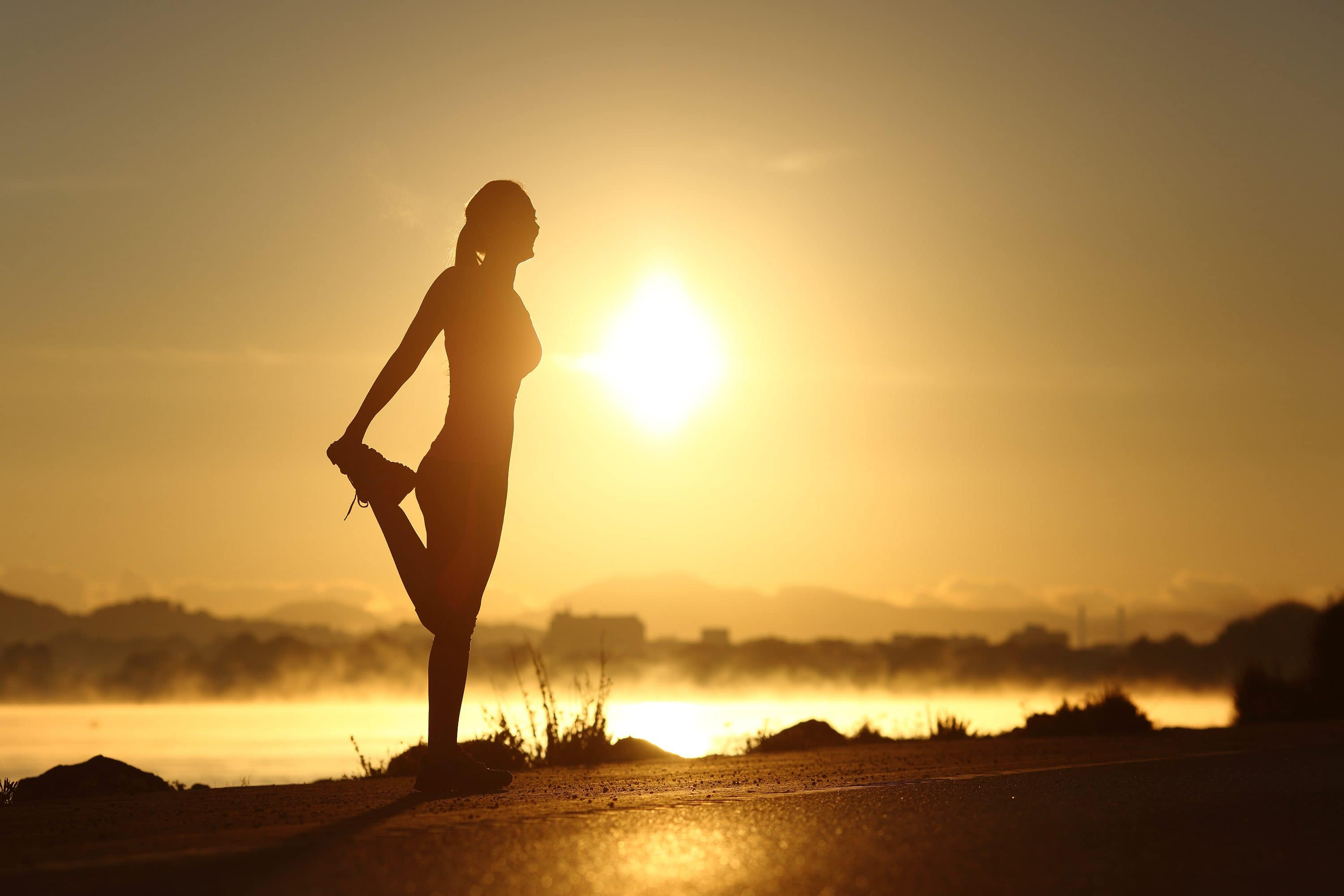 Woman stretches leg in morning sunshine