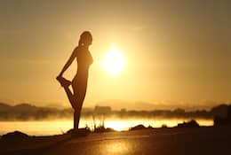 Woman stretch her leg in the morning sunshine