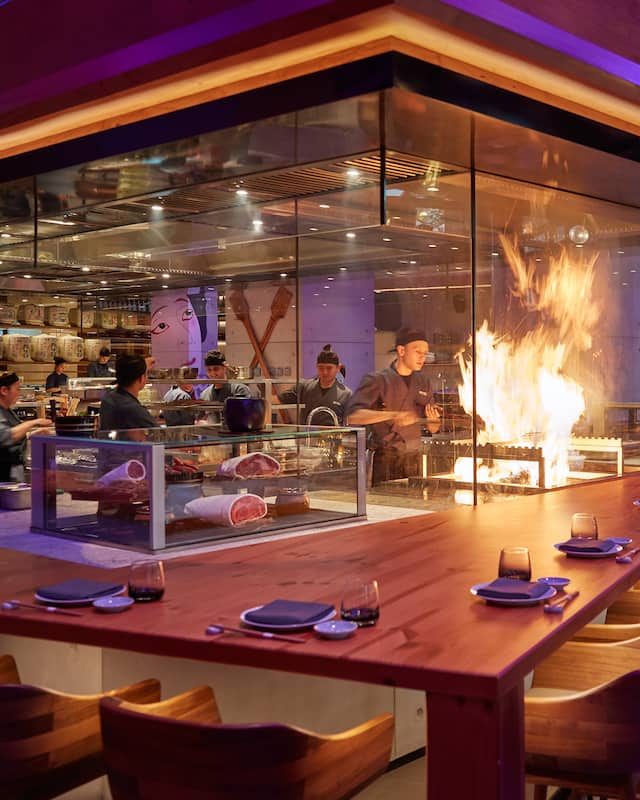Open kitchen bar at Netsu with flames coming off the grill