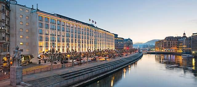 Exterior of Mandarin Oriental, Geneva, illuminated at dusk.