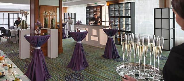 cocktail venue with purple standing tables and glasses of champagne
