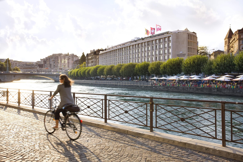 Cyclist rides along the waterfront opposite Mandarin Oriental, Geneva