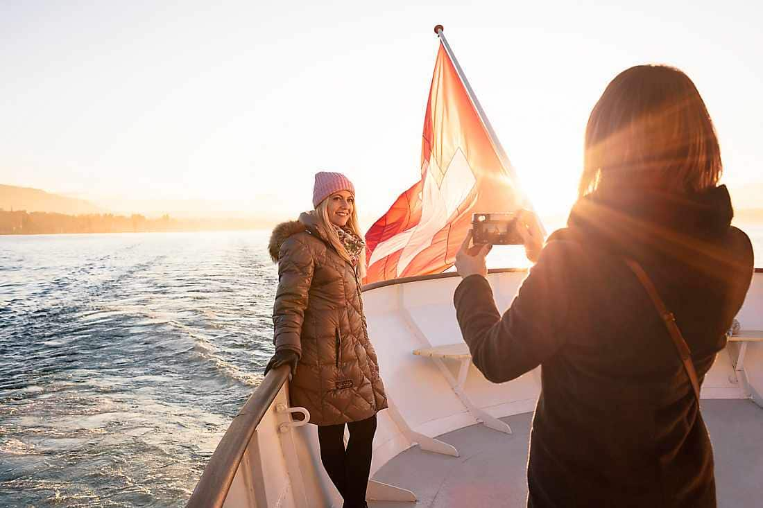 friend taking photos of her friend in the boat ride