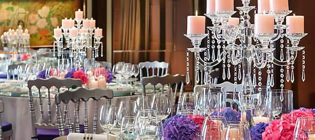 chandelier, glasses and flowers on event tables