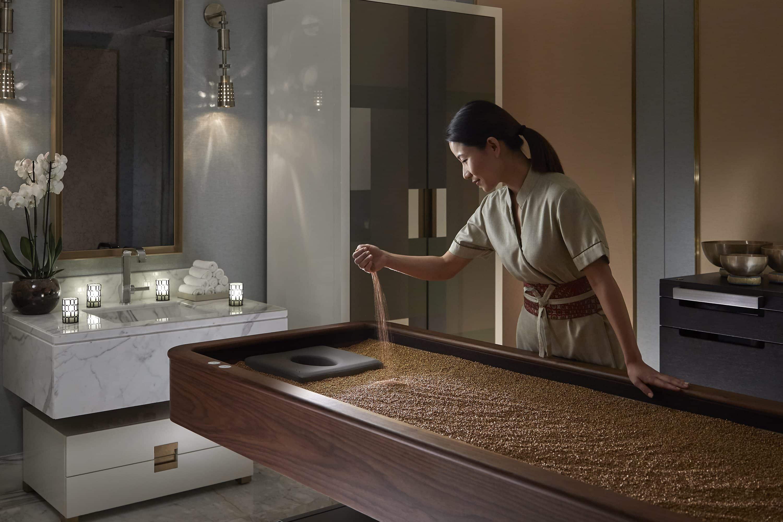 Therapist prepares quartz massage bed at The Spa at Mandarin Oriental, Doha
