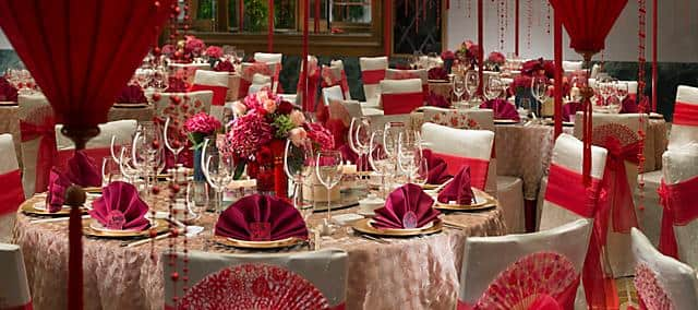 banquet table settings with red napkins and flowers