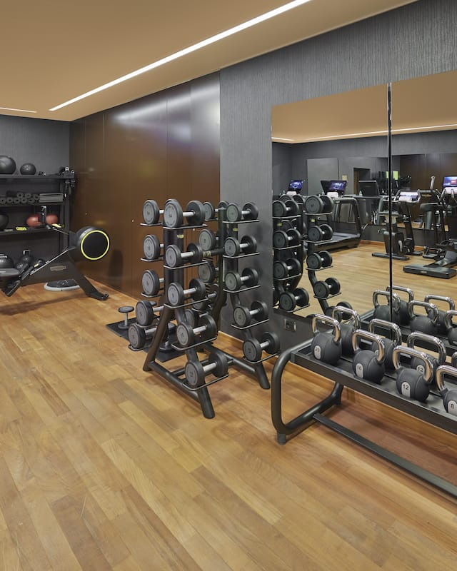 full shot of fitness centre with wood floor and racks of dumbbell