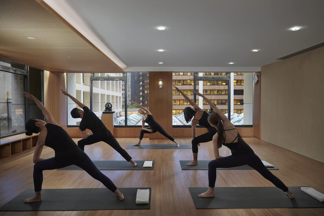 doing yoga in spa studio at the landmark mandarin oriental, hong kong
