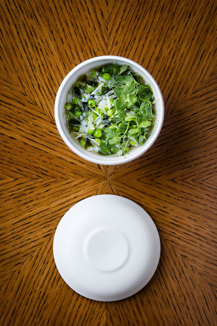 bowl of green peas on a brown table