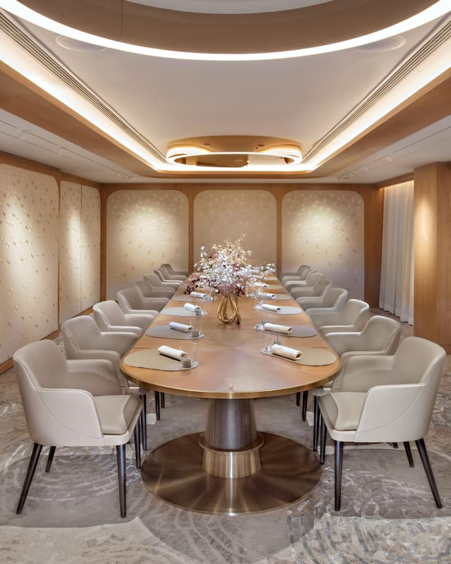 golden lit private dining room with long table surrounded by chairs