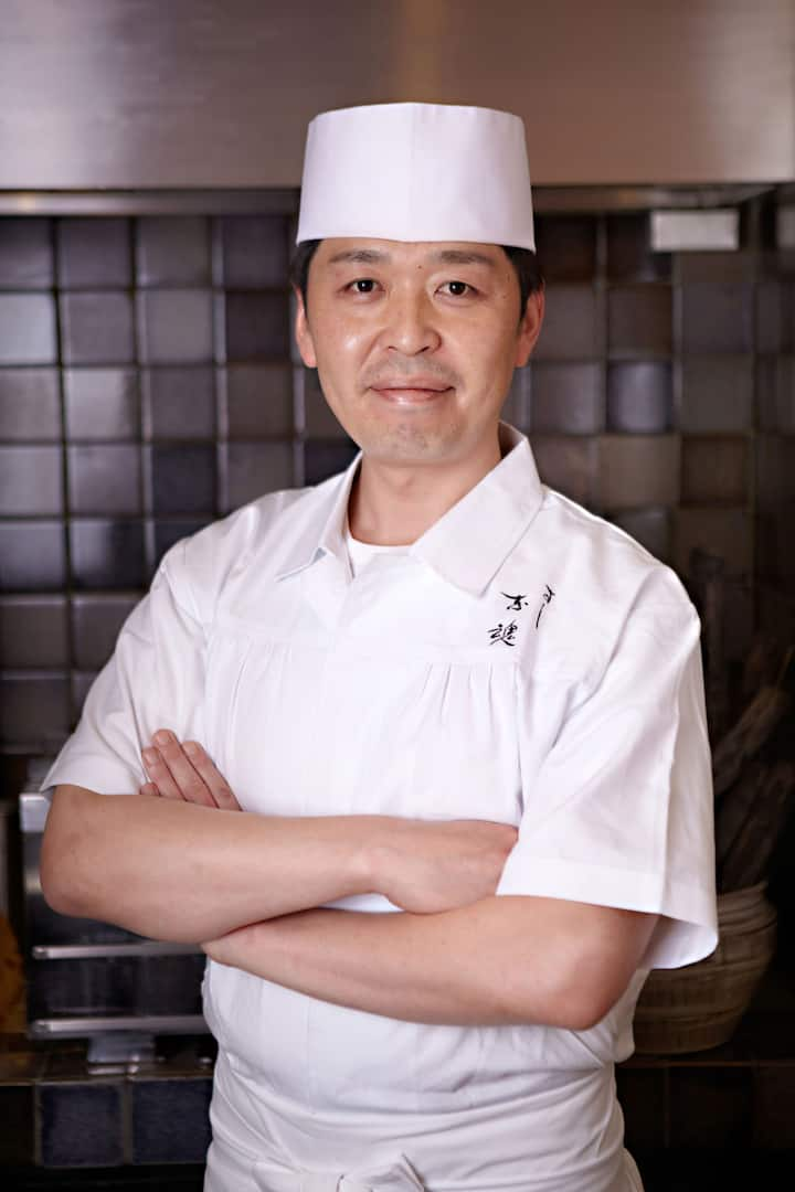 Chef Kakinuma posing with arms crossed wearing white chef hat and chef coat