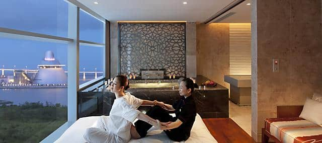 a woman getting massage treatment in spa room with spa bathtub by the side