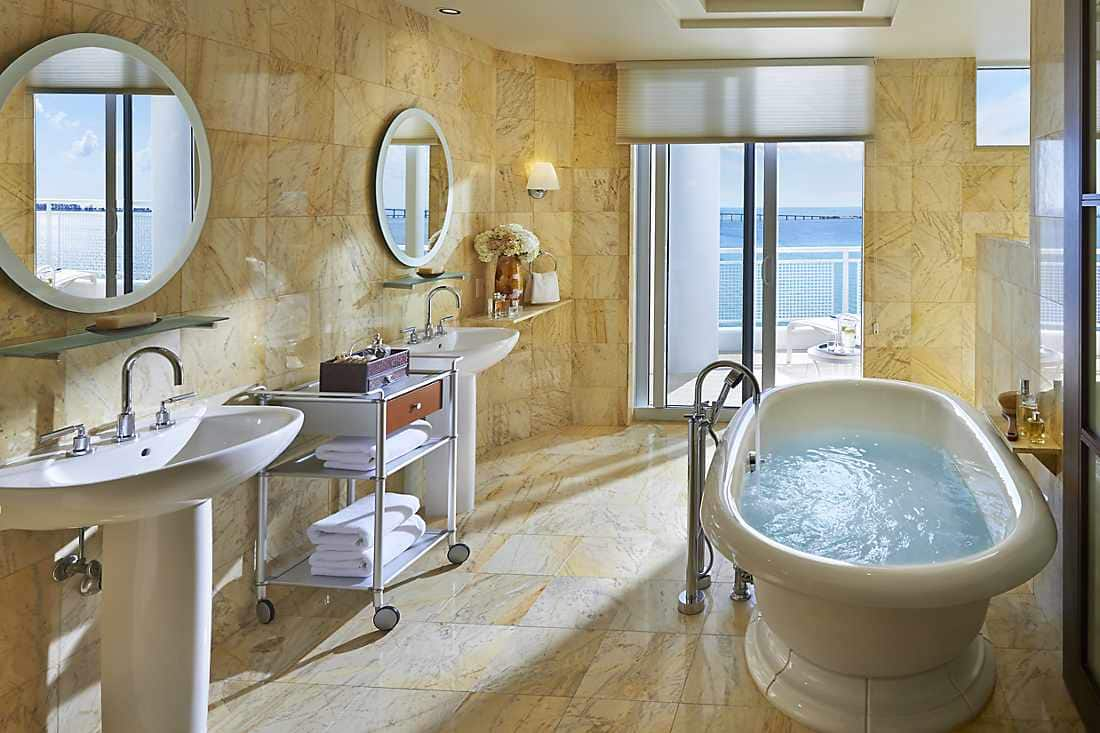 Bathroom with full bathtub and balcony views