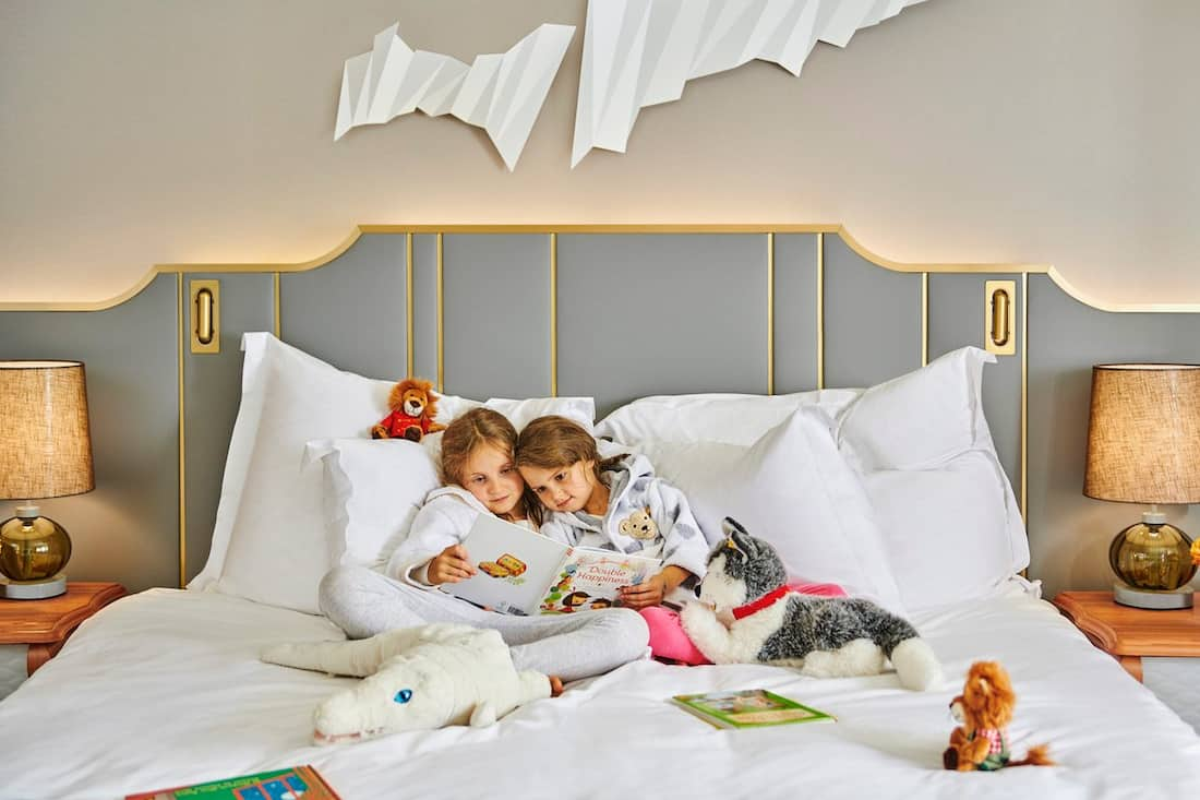 younger fans reading in bed with stuffed animals