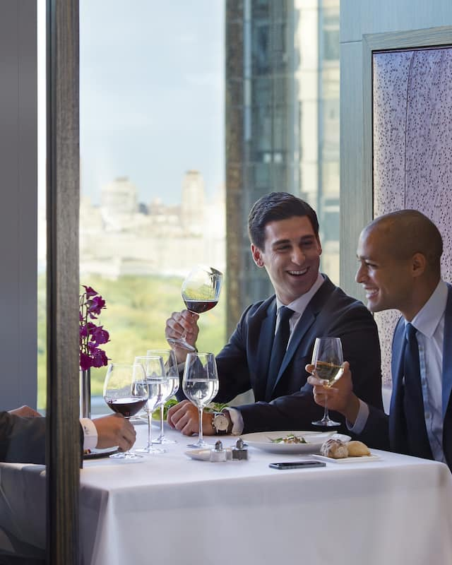 Three men in suits enjoy lunch with glasses of wines