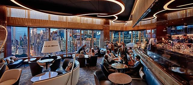 modern dining space black theme with bar and view of manhattan