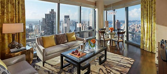 Living room and dining room in the suite overlooking manhattan and hudson river