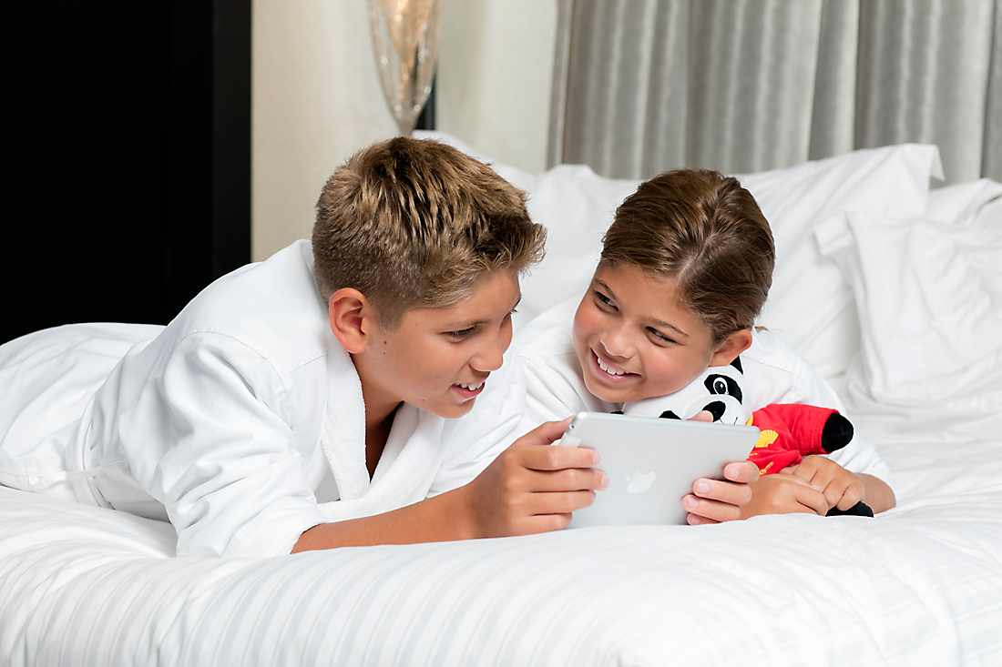 younger kids playing ipad on bed