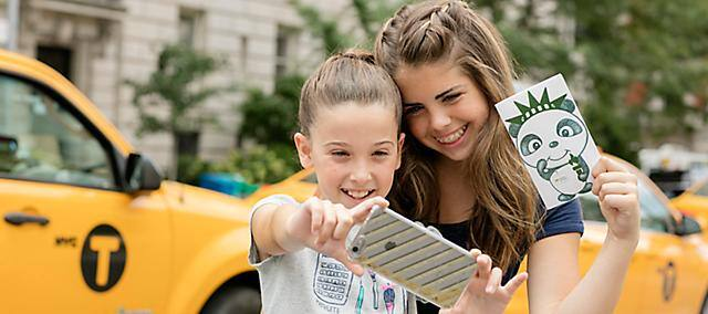 two young girls taking selfie with an iphone in front of yellow cabs