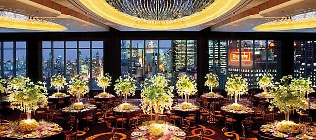 wedding venue with tables decorated by white flowers and night manhattan view
