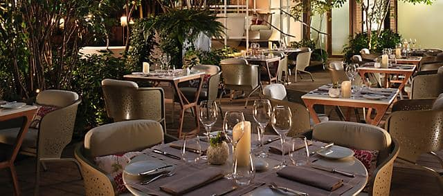 outdoor dining space around the round tables and lights at night