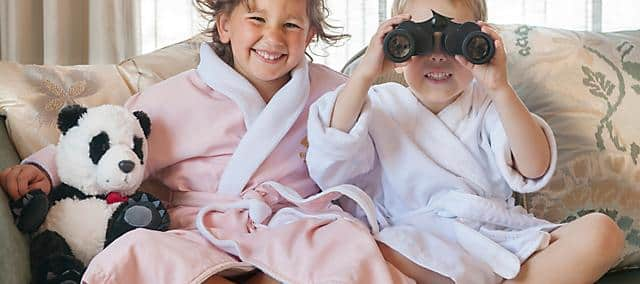 two kids in robe playing with binoculars