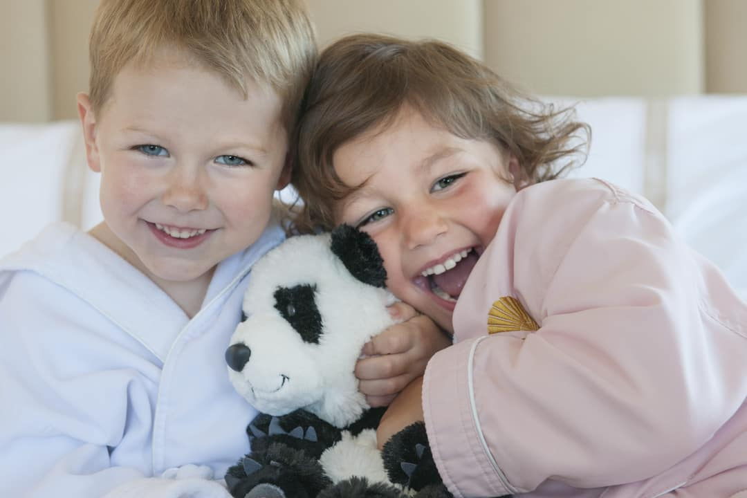 two kids happy holding panda stuffed animal