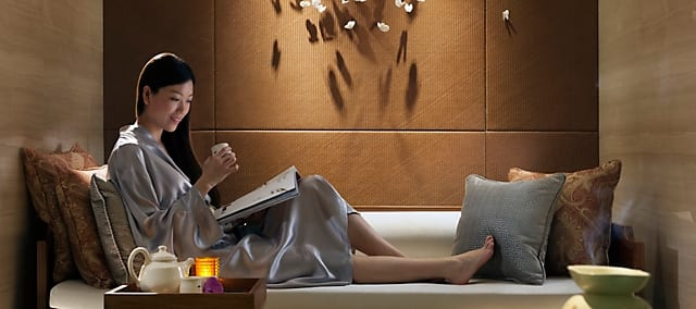 a woman drinking tea and reading magazine in the spa suite