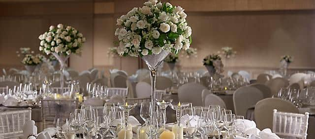 banquet table settings with white roses and glasses