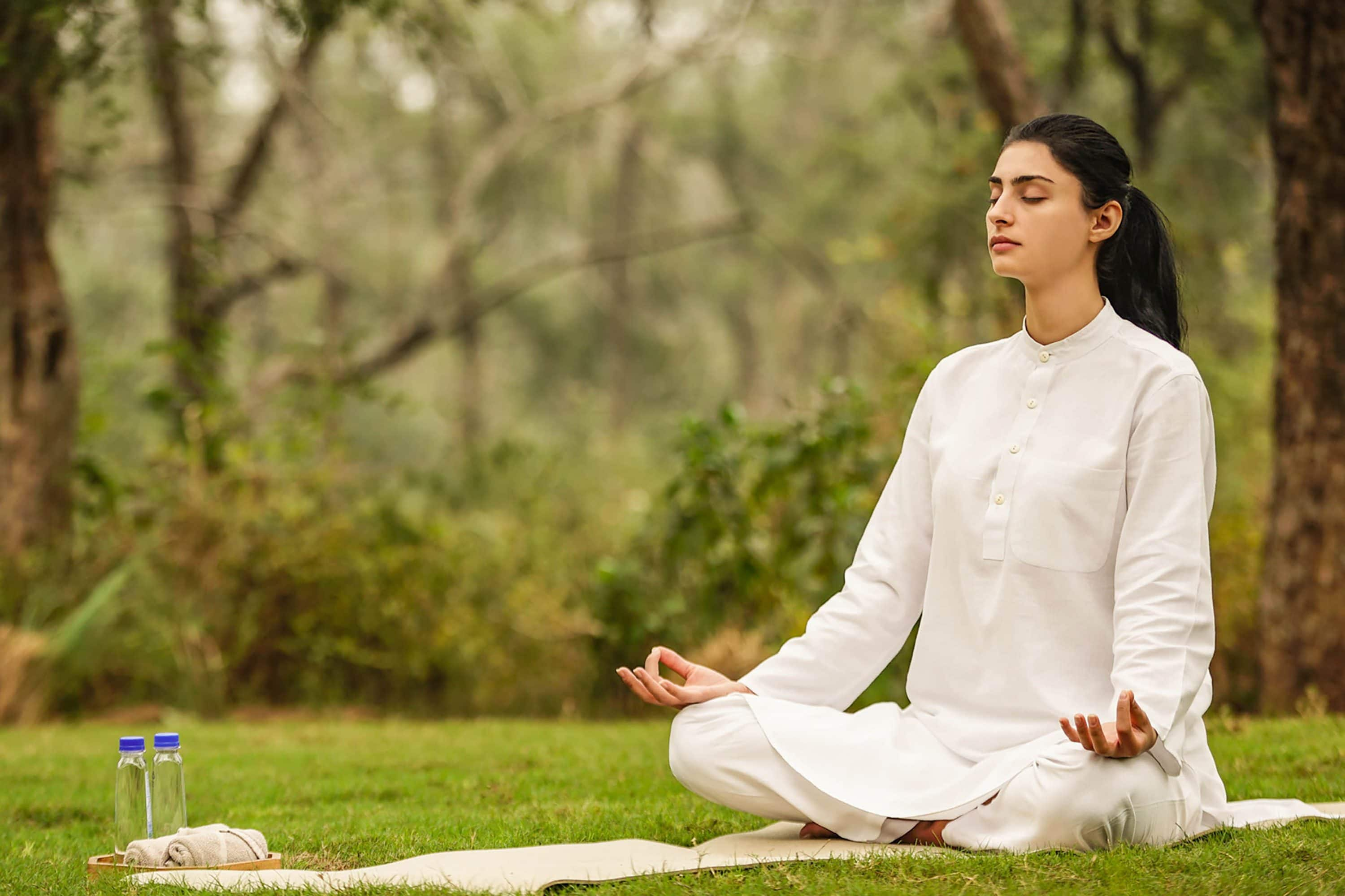 Woman practises meditation outdoors