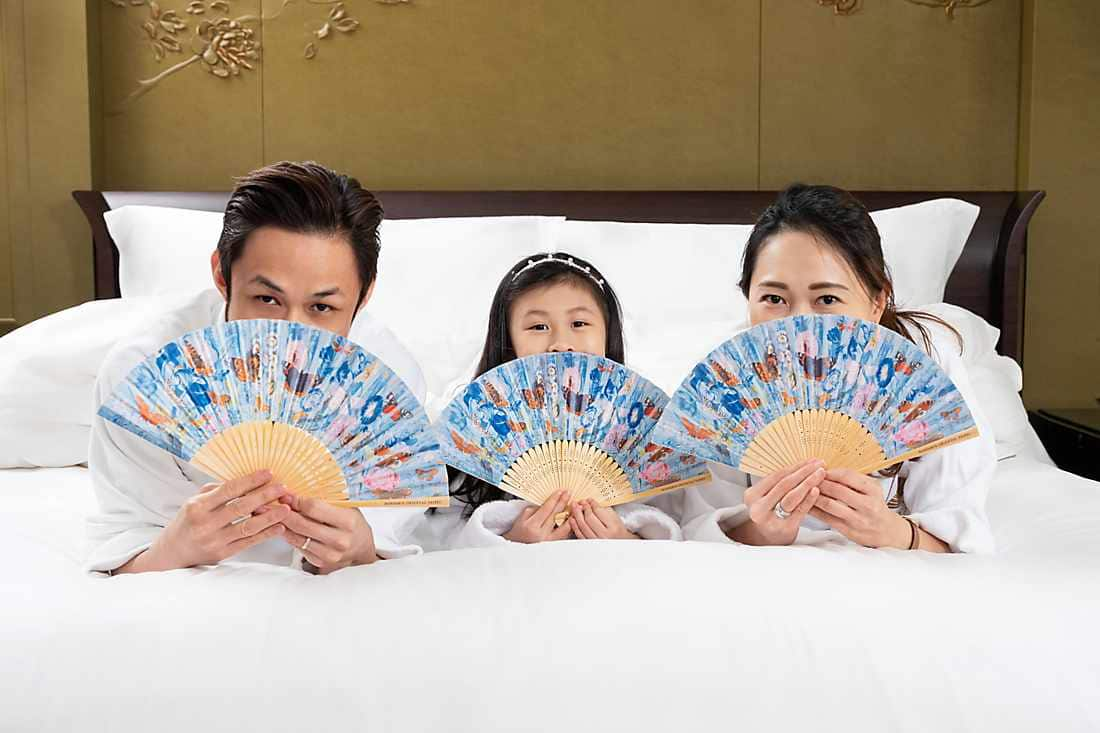 family of three have fans in their hands
