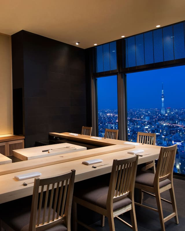 corner image of wooden bar facing window with city skyline