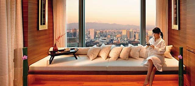 a woman sitting on spa sofa with tea overlooking Tokyo skyline