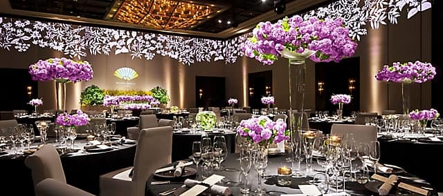 ballroom with banquet table setting and purple flowers