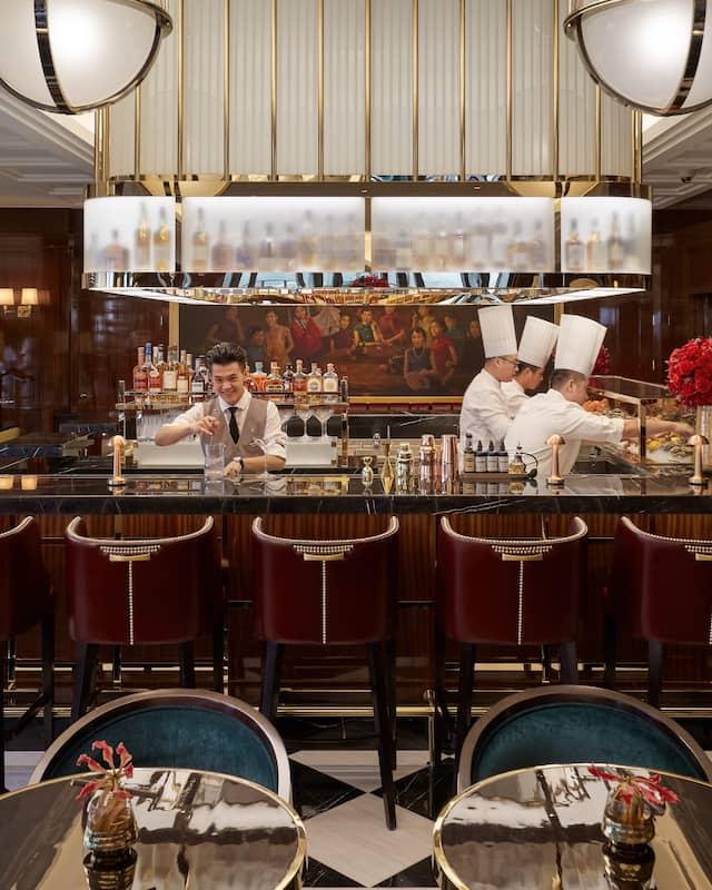 A Bar with a bartender and 3 chefs with oyster and seafood bar