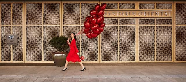 girl arriving hotel with red balloons