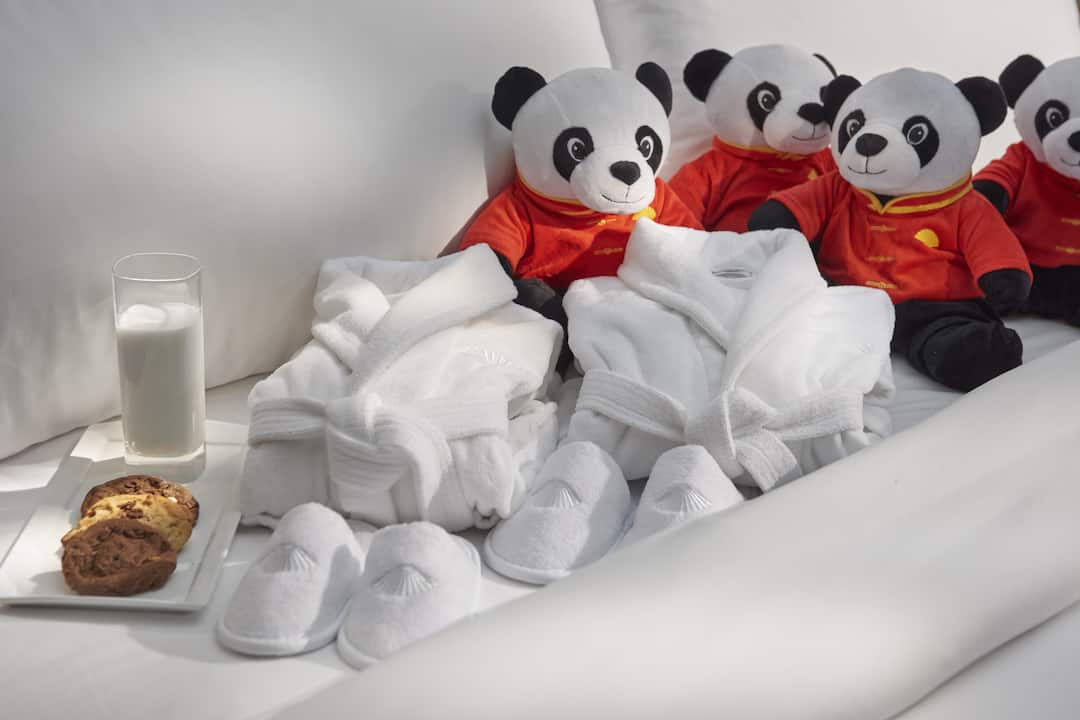 three panda dolls and towels on the bed