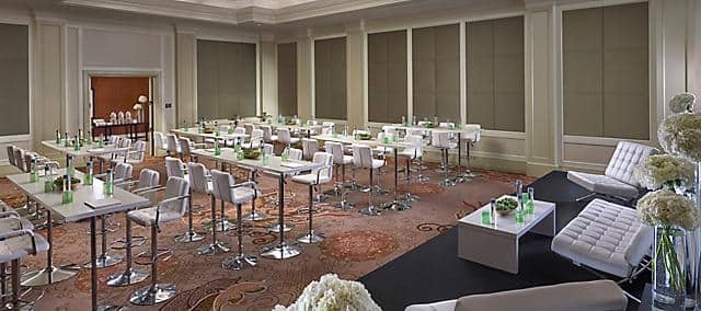 meeting room with carpet, white tables and white high chairs